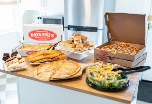 Davanni's catering spread including Pasta Pan, Group Garden Salad, Pizza, Hoagie Party Tray and Desserts