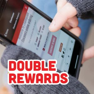 Customer holds a phone for ordering online during Double Rewards Tuesdays in March at Davanni's.